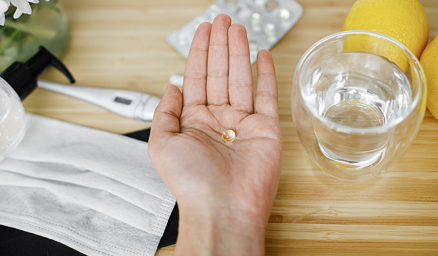 Vitamin D supplement in hand with water, lemon, thermometer, and mask on table