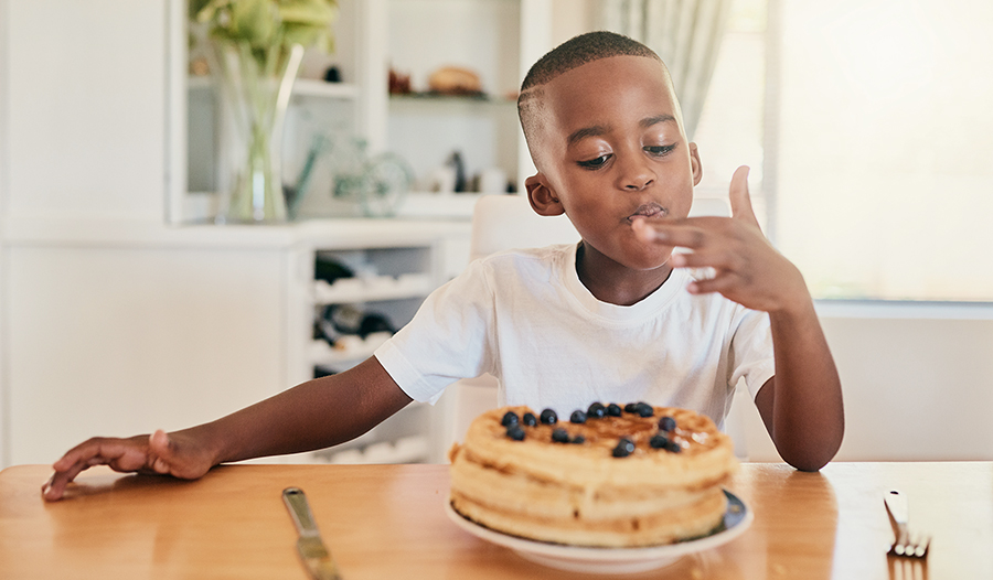 Boy eating waffles at the kitchen table at home