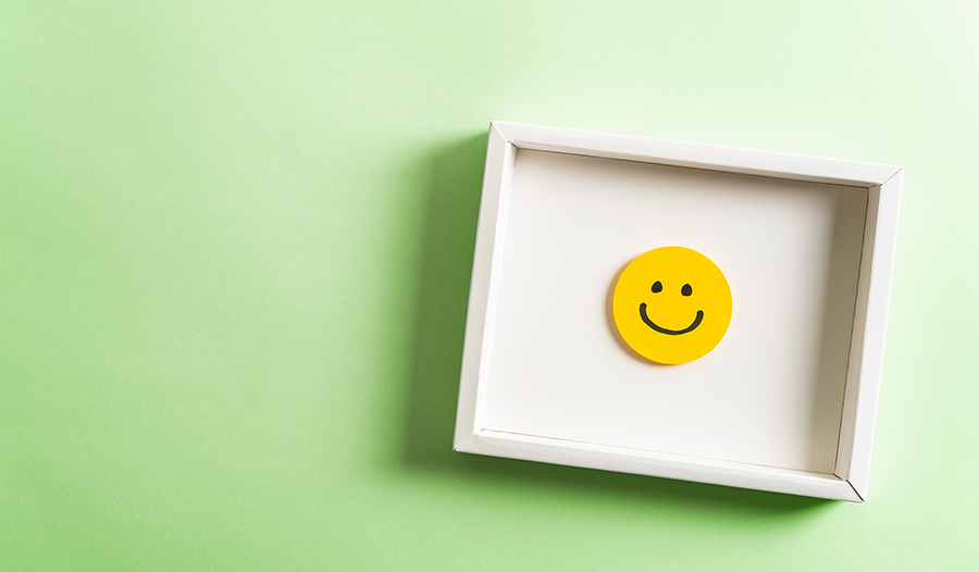 Happy yellow smiling emoticon face frame hanging on green background