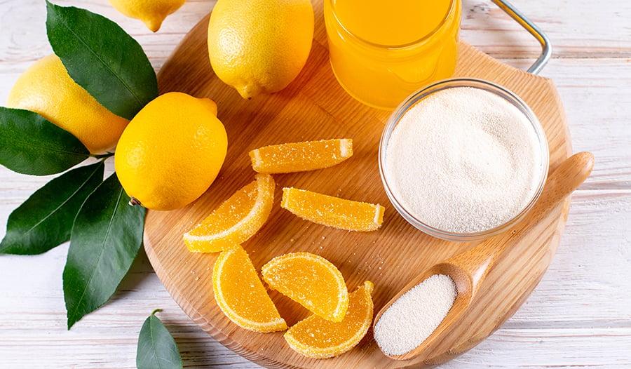 Jelly lemon candies made from gelatin powder, agar-agar, and pectin powder on wooden board