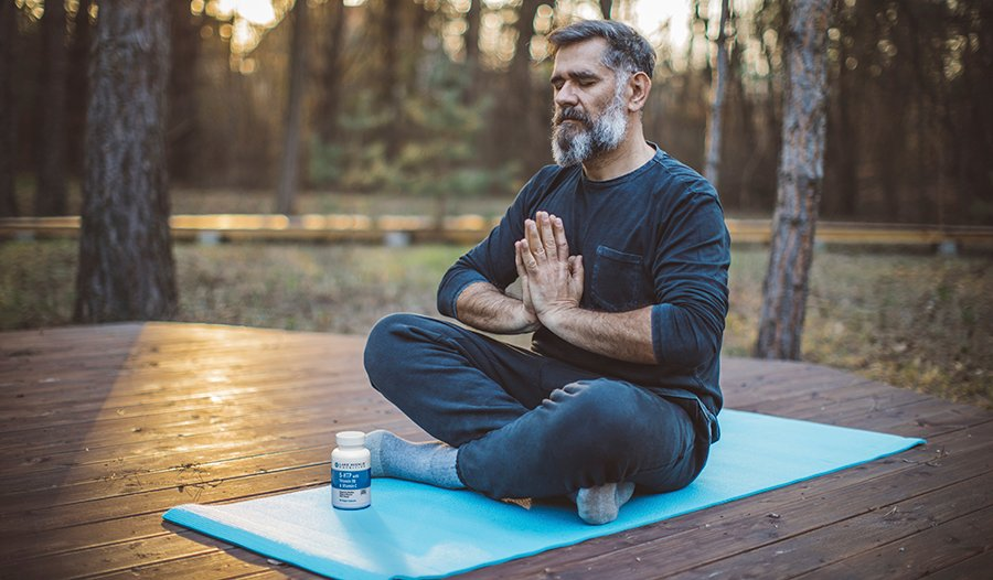 Older man meditating outside on a yoga mat with 5-HTP supplement