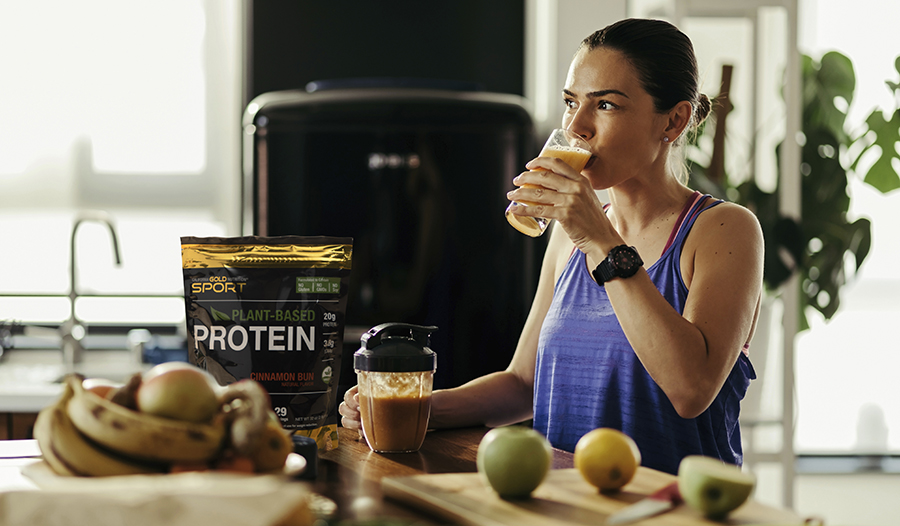 Healthy woman making a smoothie in her kitchen with plant-based protein