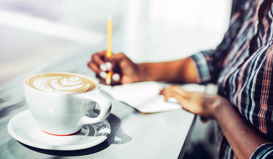 woman sitting with a latte and planning out her self-care