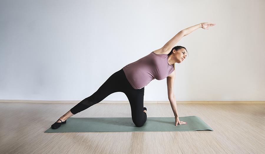 Pregnant woman doing Pilates on yoga mat