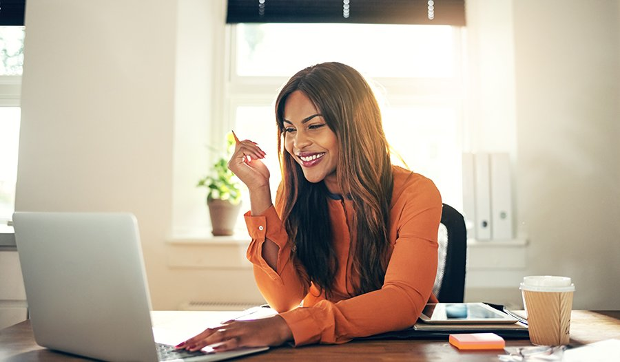 Young smiling woman in orange shirt sitting at her desk looking at a computer