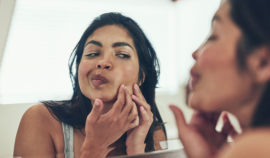 woman looking in the mirror at her adult acne
