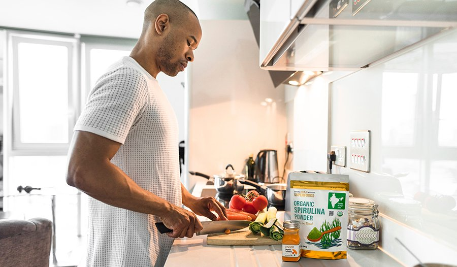 Man cooking healthy dinner in kitchen with vegetables, spirulina, and turmeric