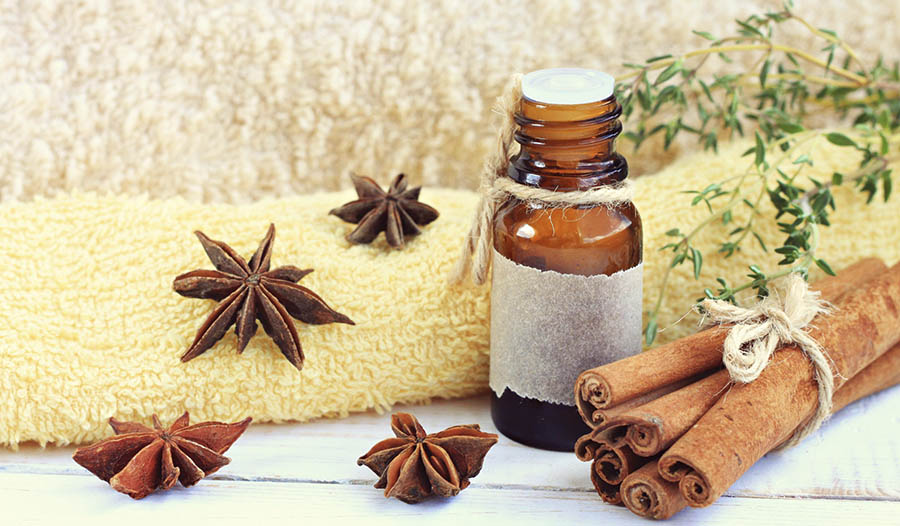 Cinnamon essential oil with towel and cinnamon cloves