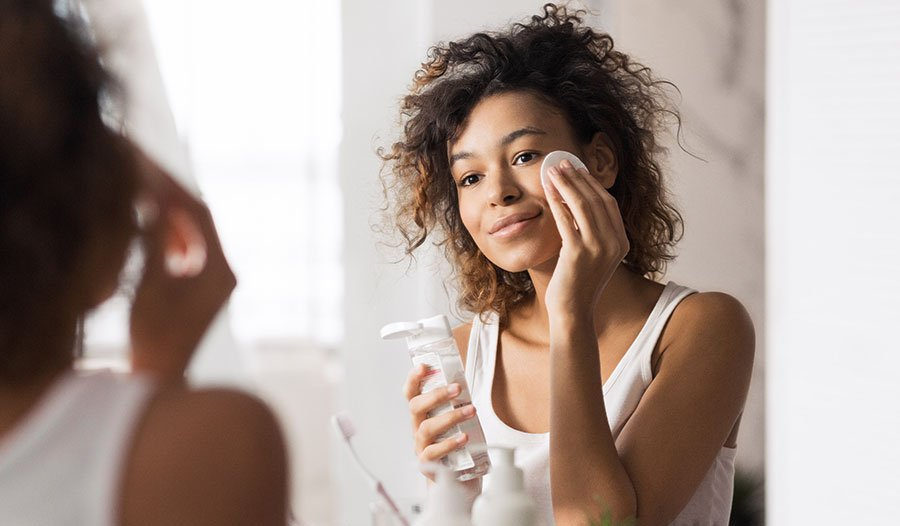 woman applying micellar water on a cotton pad to her sensitive skin