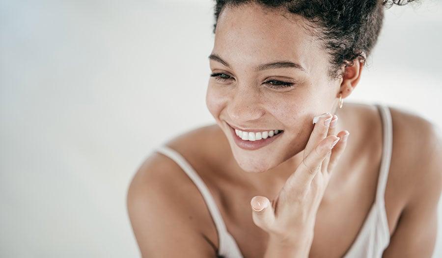woman applying beta glucan moisturizer to her face