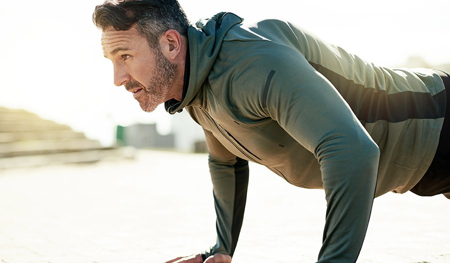 Mature man doing push ups outdoors