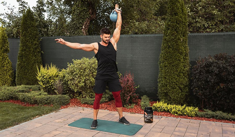 Male athlete working out in backyard with kettlebell