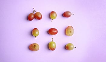 red grapes on purple background