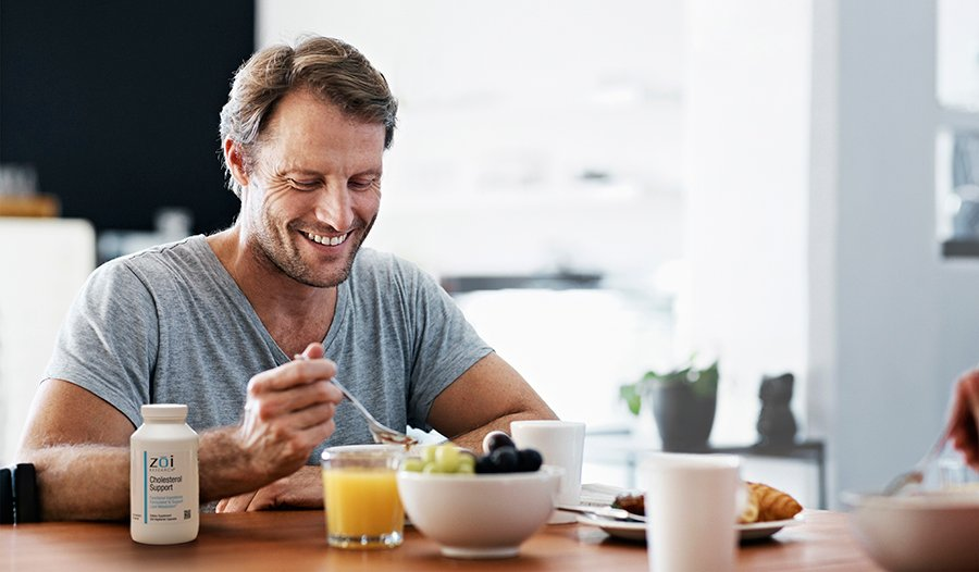 Man eating healthy breakfast with cholesterol support supplement on table