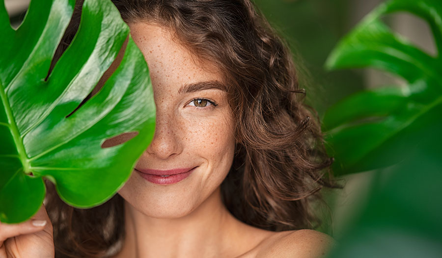 woman with monsterra plant leaf in front of one eye