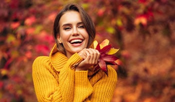 woman in yellow sweater holding autumn leaves