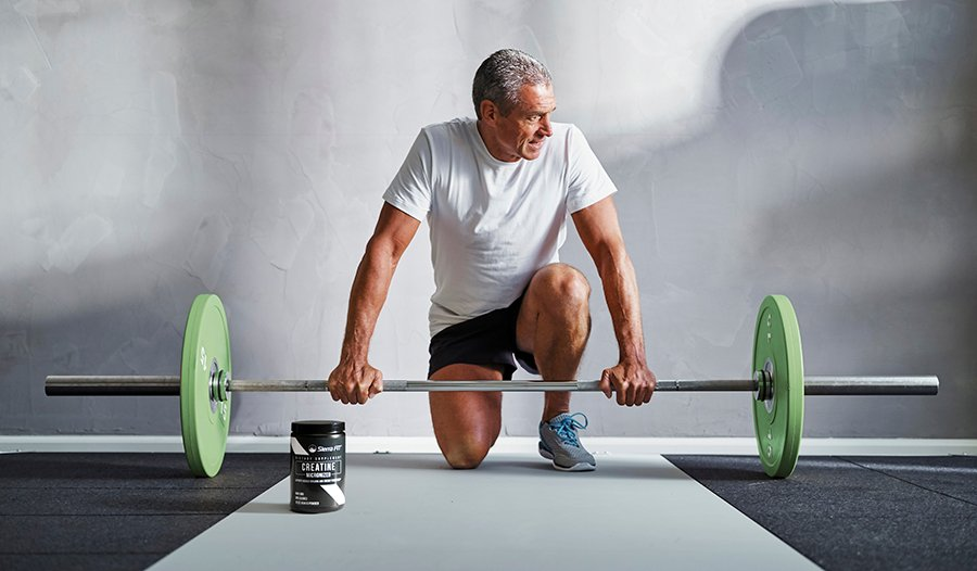 Mature male strength training with barbell in the gym