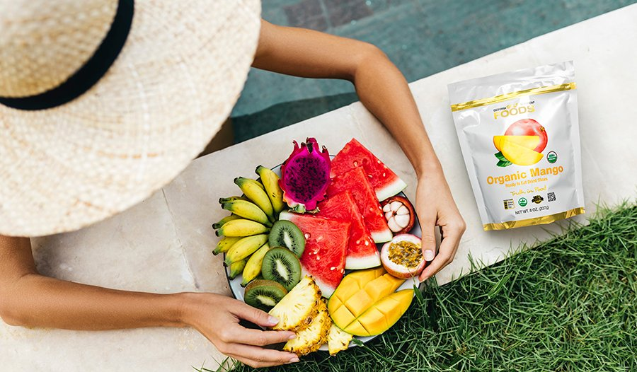 Overhead shot of woman wearing sun hat eating plate of fruit in the pool