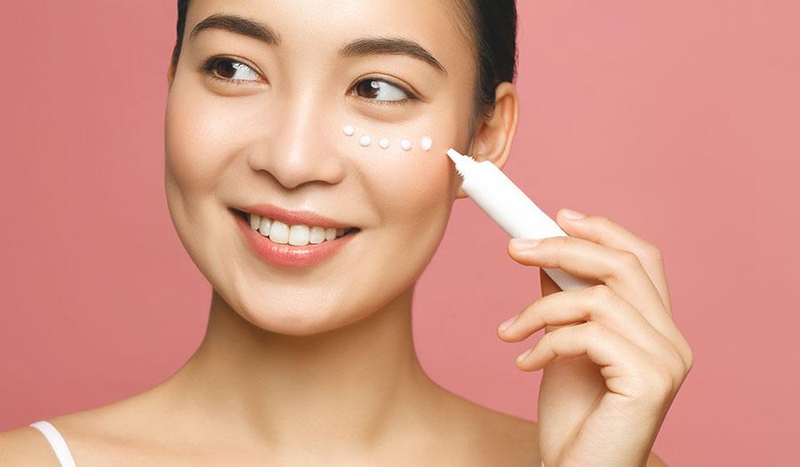 woman applying eye cream in a few dots under her eye