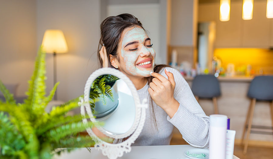 woman applying green tea mask to her face