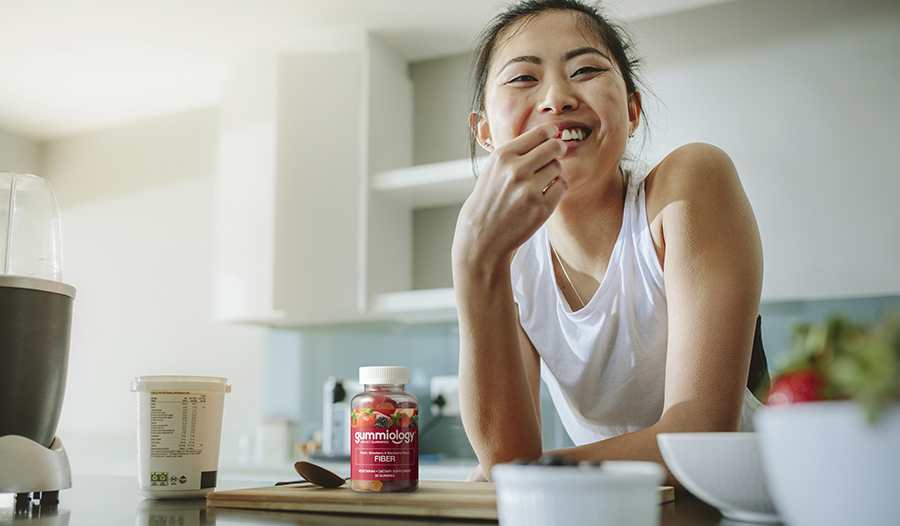 Healthy woman eating breakfast in her kitchen with yogurt and fiber supplement on counter