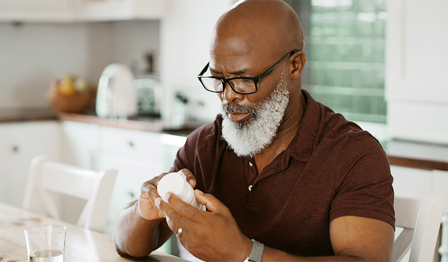 Mature man with glasses examines supplement bottle