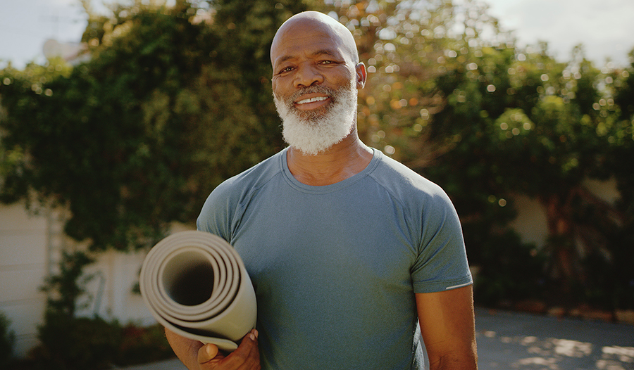 Healthy older man standing outside before a yoga session in his backyard