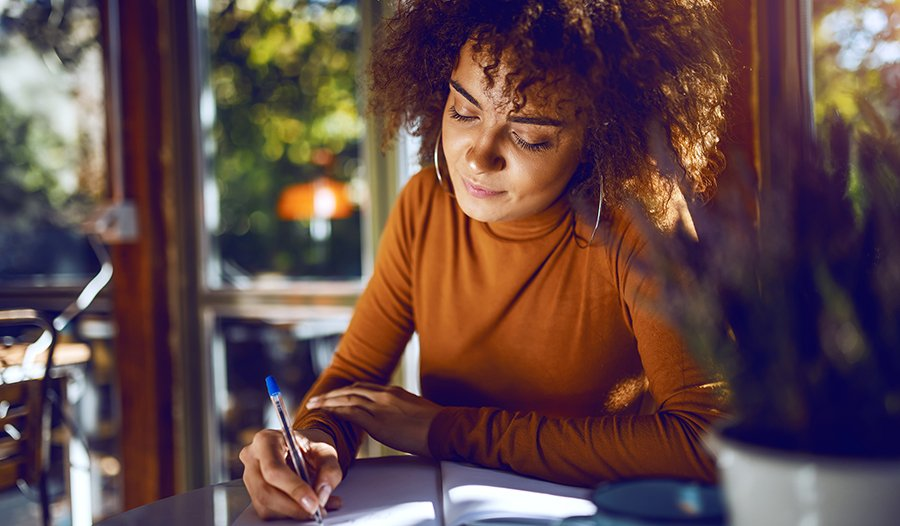 Woman sitting outside at cafe writing in journal