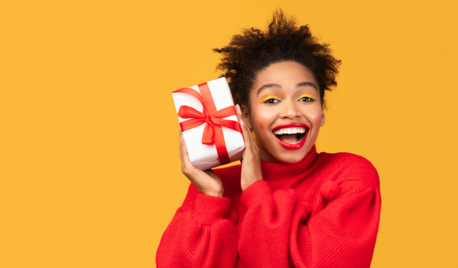 woman against yellow background holding up an unopened self-care gift