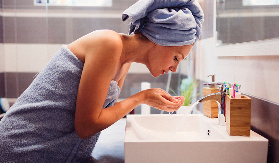 woman in bath towel washing face at sink with oil cleanser