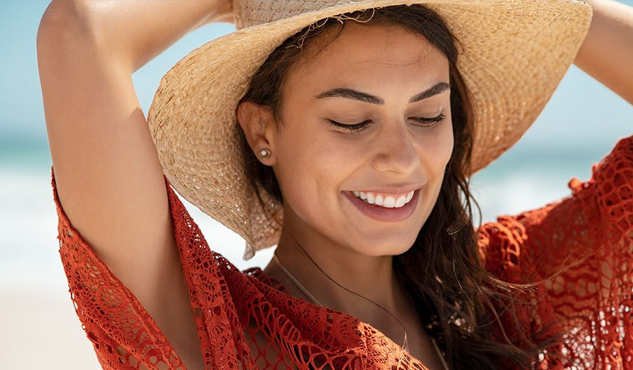 woman at the beach wearing a sun hat to prevent sun burn
