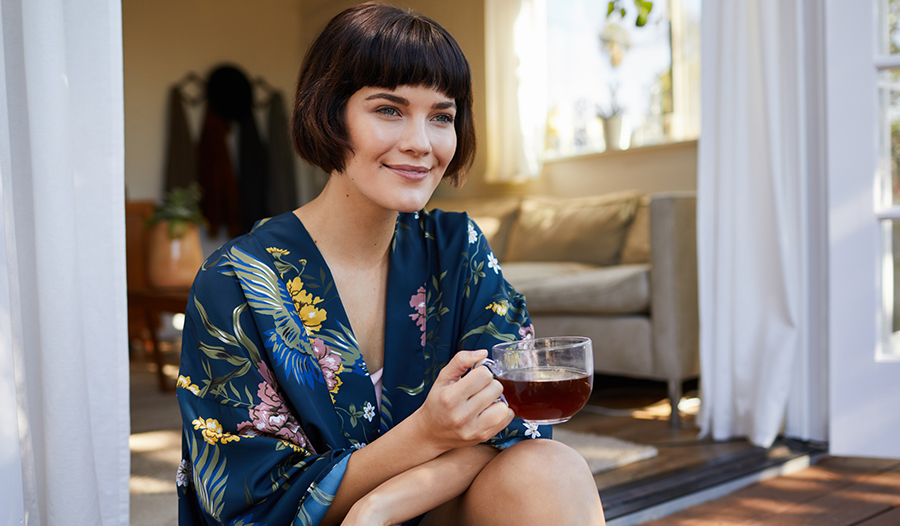 woman in floral robe sitting outside with cup of tea contemplating self-care