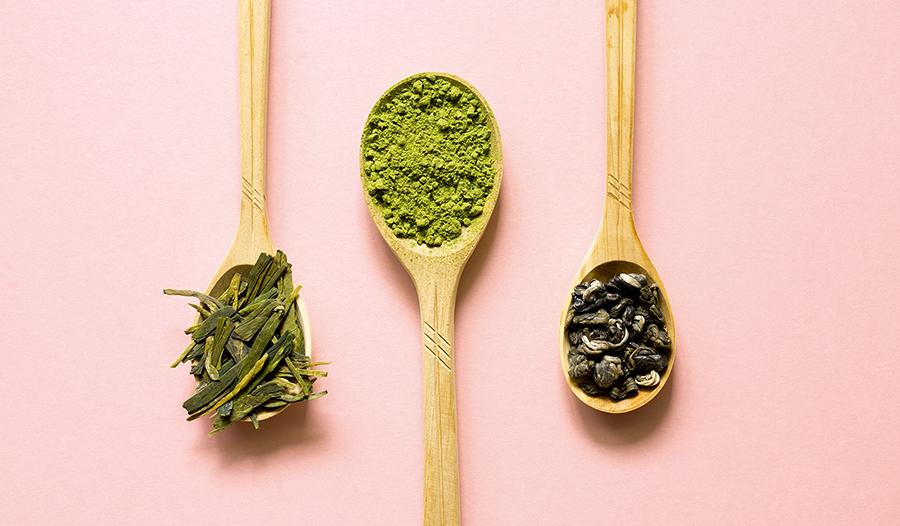 Wooden spoons of Biluochun, Matcha (powdered green tea) and Longjing on a pink background