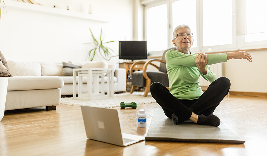 Elderly woman doing yoga video stretching at home on yoga mat