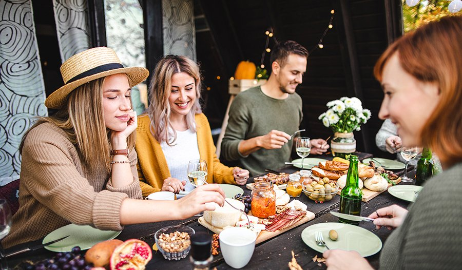 Group of friends sharing healthy cheese board