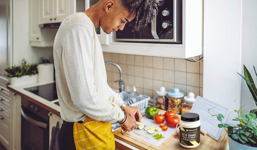 Man wearing apron cutting vegetables in kitchen with shake powder on counter