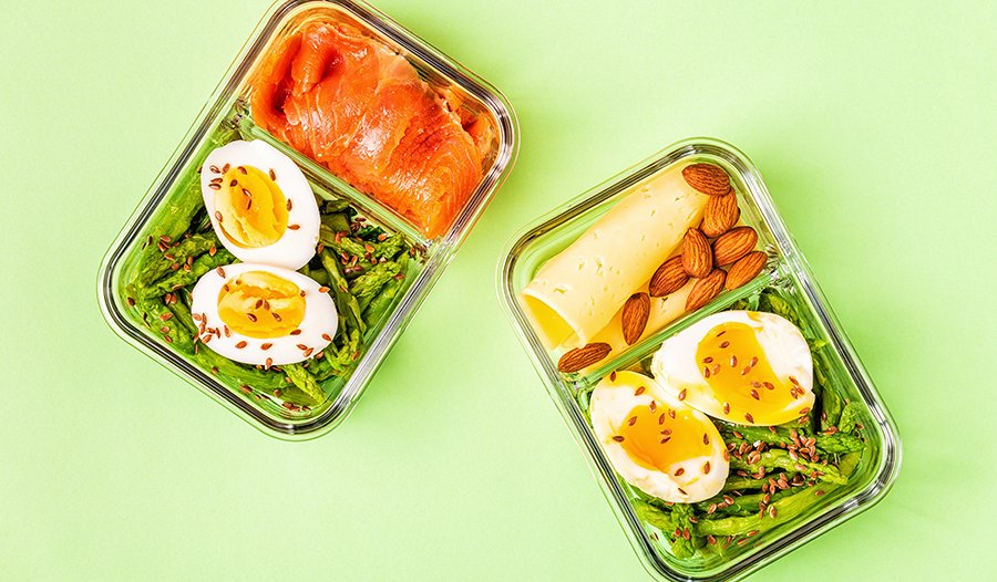 Healthy keto lunchbox with eggs, salmon asparagus, flax seeds