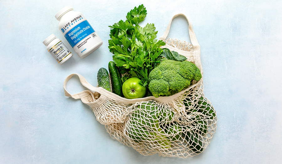 Green vegetables in reusable bag on table with supplements
