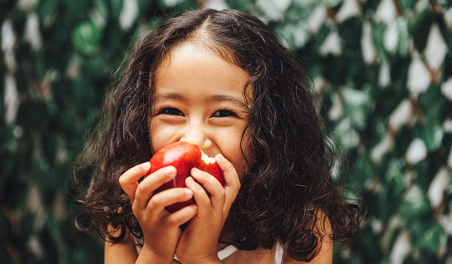 Little girl with curly hair eating a red apple