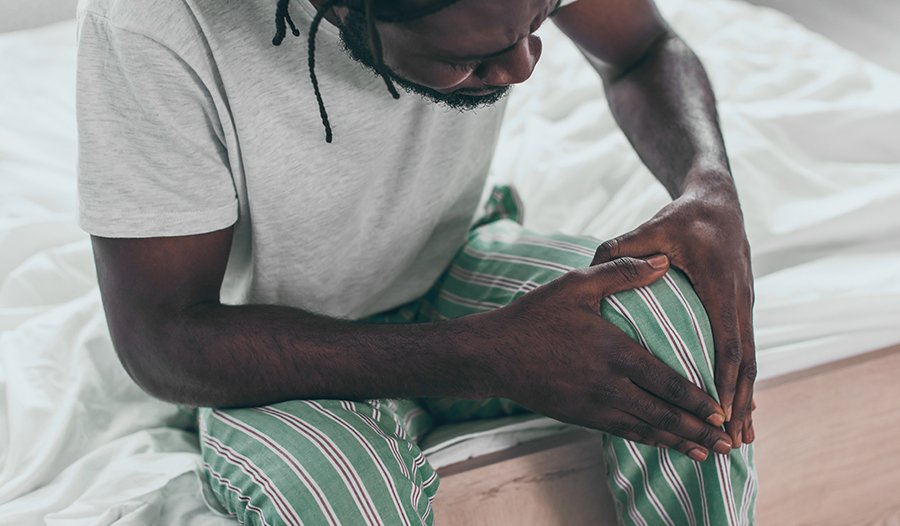 Young man with knee pain sitting on bed in pajamas
