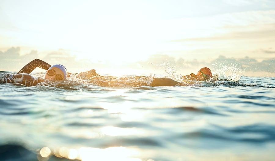 Healthy women swimming in the ocean wearing swim caps and wet suits