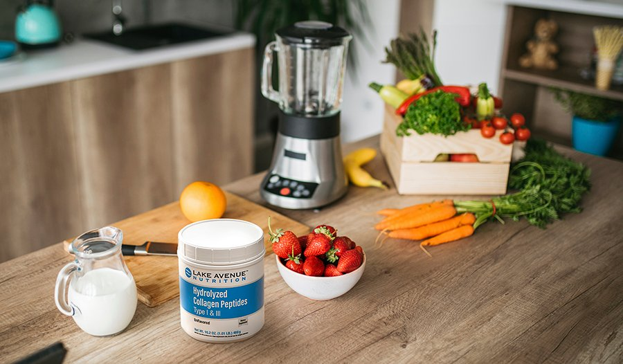 Kitchen counter with smoothie ingredients like collagen, vegetables, milk, and fruit