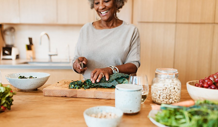 Mature woman preparing healthy kale vegetable salad in kitchen