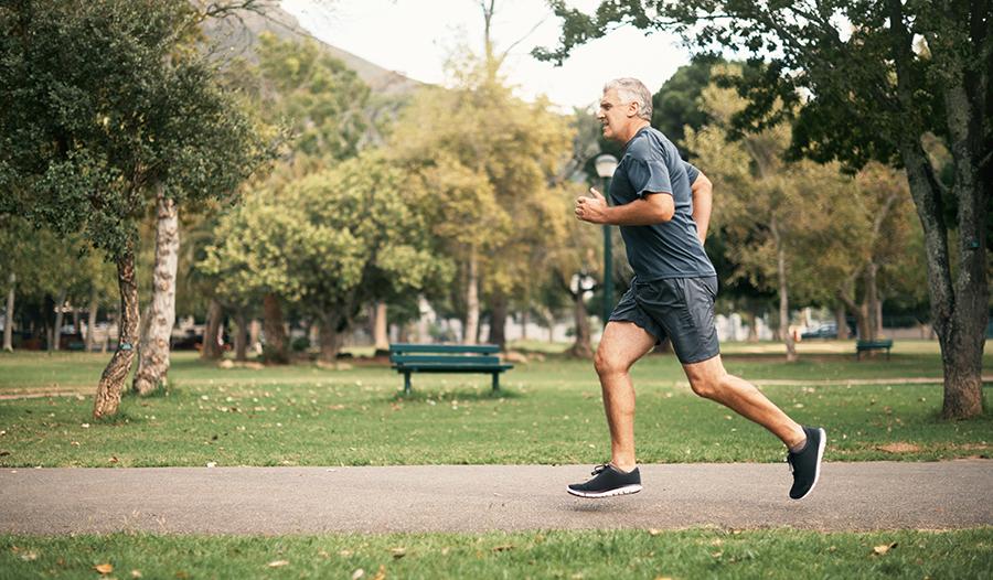 Healthy senior man running through green park