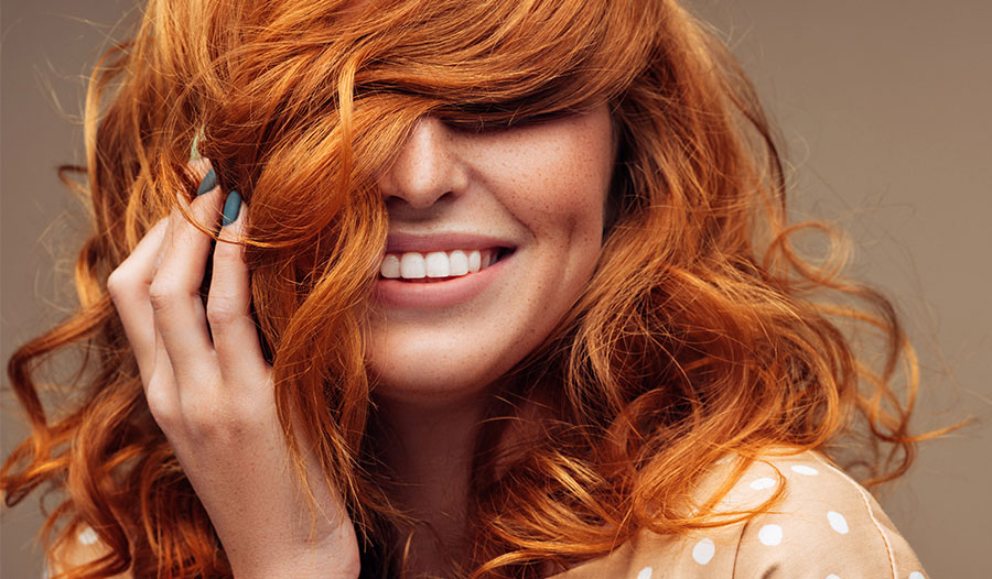 woman with red hair smiling at camera with hair over her eyes
