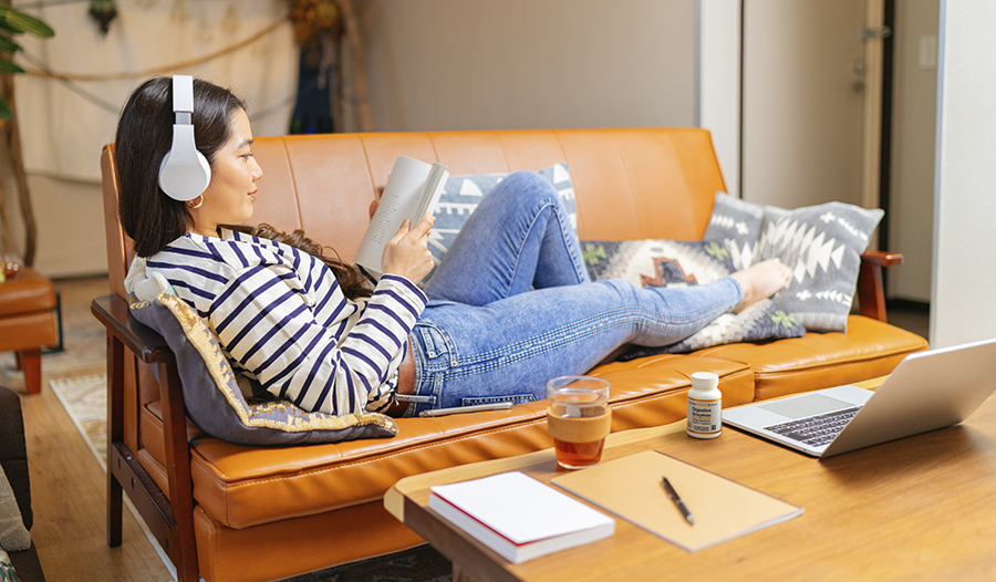 Woman with headphones on laying on couch reading with tea and digestive enzymes on table