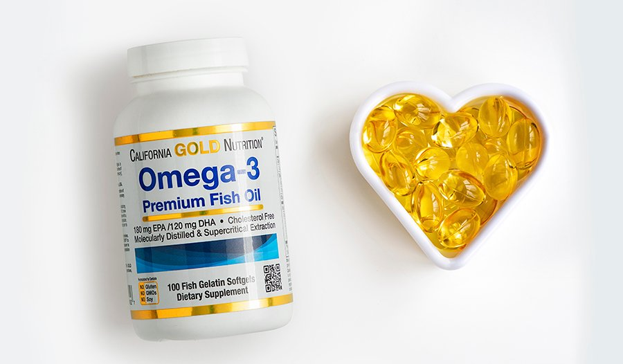 Omega-3 fish oil supplements in heart container on white background