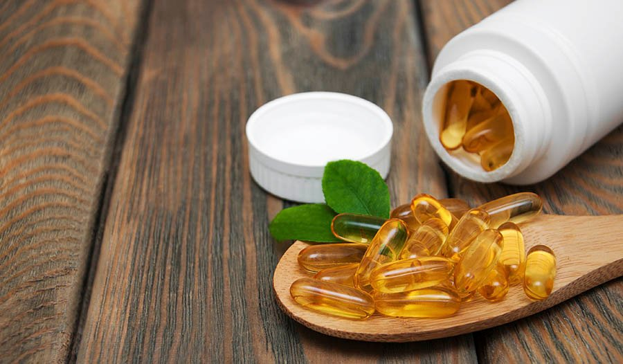 Fish Oil omega-3 fatty acid capsules and bottle on wooden table