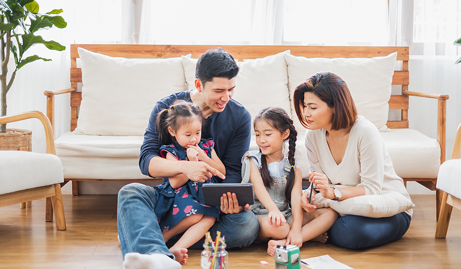 Happy Asian family learning from home with iPad tablet