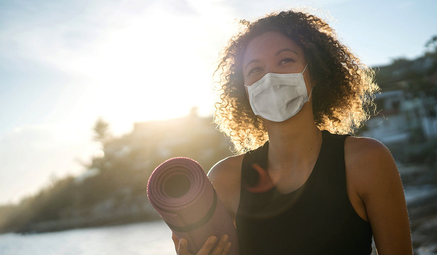 woman wearing a mask and carrying yoga mat about to practice self-care